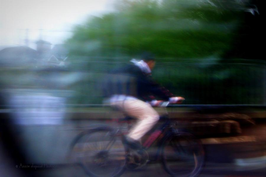 man on a bicycle, image taken from a car